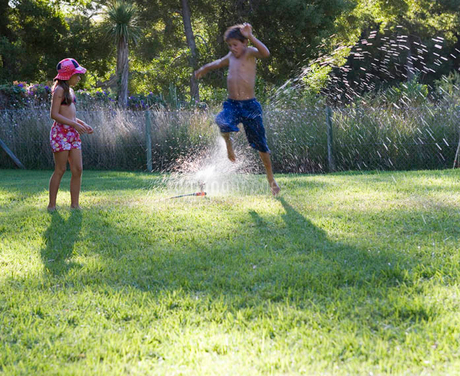 Young boy and girl playing with water in the gardenの写真素材 [FYI02119098]