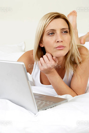 Young woman in bed working on laptopの写真素材 [FYI02119123]