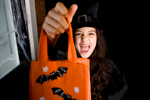 Girl in costume at a Hallowe'en party, holding an orange party bagの写真素材 [FYI02119149]