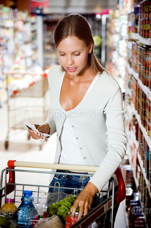 Woman putting shopping into a supermarket trolleyの写真素材 [FYI02119150]