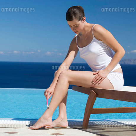 A woman shaving her legs by a poolの写真素材 [FYI02119158]