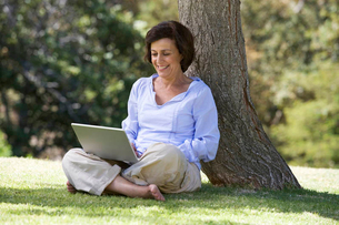 A senior woman sitting under a tree using a laptopの写真素材 [FYI02119177]