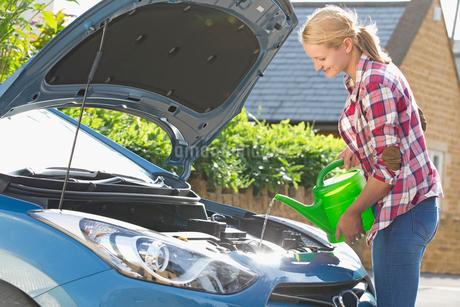 Woman Filling Car Radiator With Waterの写真素材 [FYI02119188]