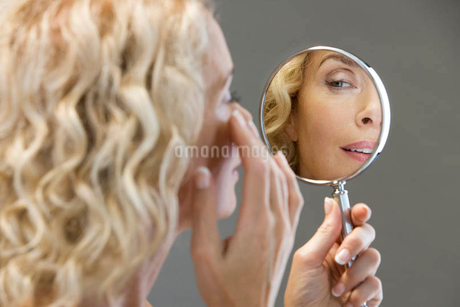 A middle-aged woman looking at her face in the mirrorの写真素材 [FYI02119203]