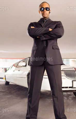 A chauffer standing by a stretch limousineの写真素材 [FYI02119223]