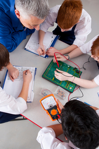 Teacher watching students working on electronic device in vocational classの写真素材 [FYI02119253]