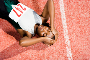 Female athlete resting on a running trackの写真素材 [FYI02119254]