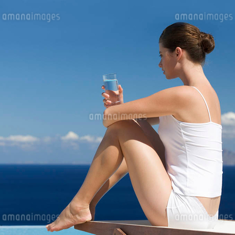 A woman relaxing by a poolの写真素材 [FYI02119304]