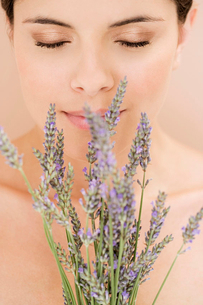Young woman smelling lavender flowersの写真素材 [FYI02119314]