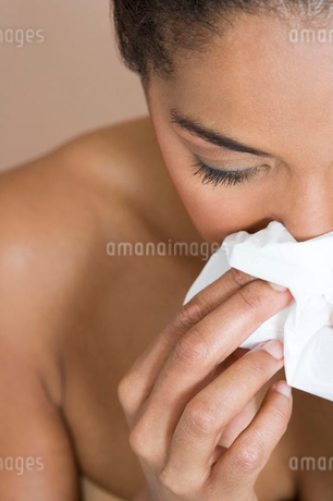 A woman blowing her noseの写真素材 [FYI02119339]