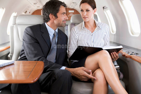 A businessman flirting with his PA on a flightの写真素材 [FYI02119350]
