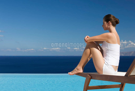 A woman relaxing by a poolの写真素材 [FYI02119360]