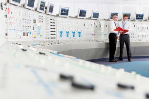Engineers discussing paperwork in control room of nuclear power stationの写真素材 [FYI02119367]