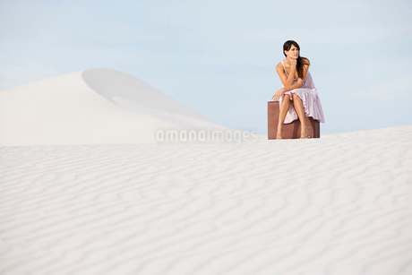 A young woman sitting on a suitcase in the desertの写真素材 [FYI02119369]