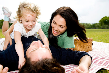 family play fighting on picnic rugの写真素材 [FYI02119377]