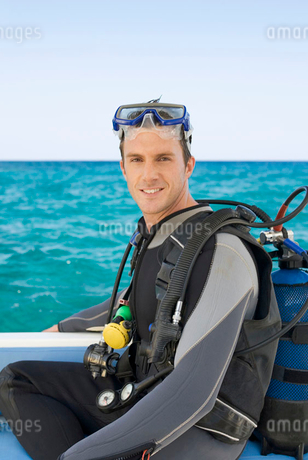 A man sitting on a boat about to go scuba divingの写真素材 [FYI02119386]