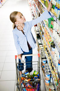 Young girl reaching up to get something off of a supermarket shelfの写真素材 [FYI02119387]