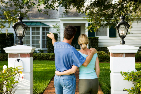 Couple standing on the garden path outside their new homeの写真素材 [FYI02119391]