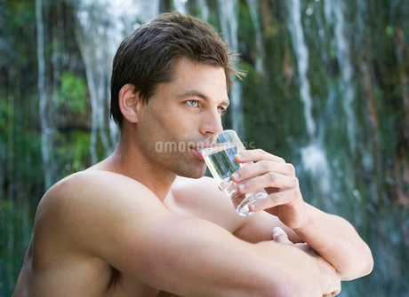 A man drinking water by a waterfallの写真素材 [FYI02119397]