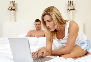 Young couple in bedroom, working on laptopの写真素材 [FYI02119419]