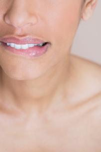 A woman biting her lip, looking worriedの写真素材 [FYI02119421]