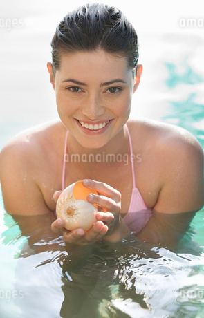 A woman in a pool holding a shellの写真素材 [FYI02119468]