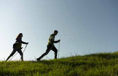 A couple out hiking, using walking polesの写真素材 [FYI02119477]