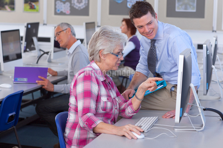 Teacher talking with adult student in college evening class computer labの写真素材 [FYI02119488]