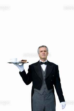 Mature butler with tray of tea, cut outの写真素材 [FYI02119502]
