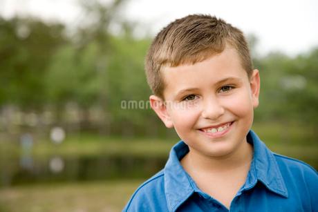 portrait boy smiling standing in parkの写真素材 [FYI02119512]
