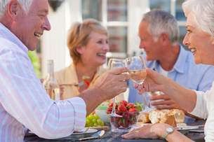 Senior couples drinking wine and enjoying lunch on sunny patioの写真素材 [FYI02119520]