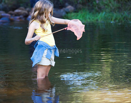 A young girl standing in a river with a fishing netの写真素材 [FYI02119538]