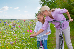Mother and daughter with bicycles looking at wildflowers in fieldの写真素材 [FYI02119567]