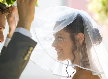 A groom lifting the veil of his brideの写真素材 [FYI02119570]