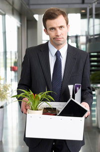 A redundant businessman taking his belongings home in a boxの写真素材 [FYI02119572]