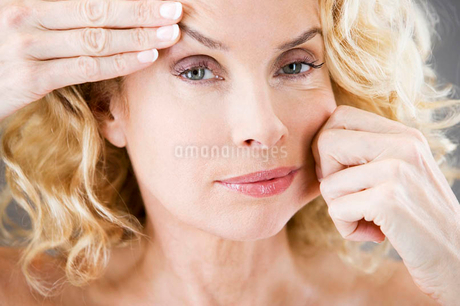 A middle-aged woman pulling the skin on her faceの写真素材 [FYI02119587]