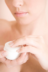 Young woman with pot of moisturising creamの写真素材 [FYI02119594]