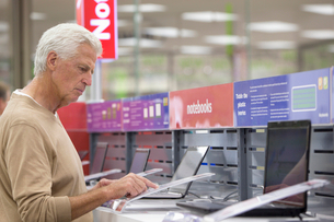 Senior man looking at prices on laptops in electronics storeの写真素材 [FYI02119603]