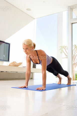 Mature woman doing push-ups on exercise mat in living roomの写真素材 [FYI02119609]