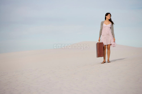 A young woman walking in the desert carrying a suitcaseの写真素材 [FYI02119615]