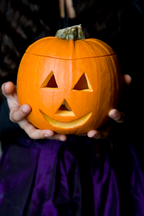 Child holding Hallowe'en pumpkin with a carved faceの写真素材 [FYI02119621]