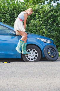Frustrated Woman Broken Down With Flat Tyre On Carの写真素材 [FYI02119628]