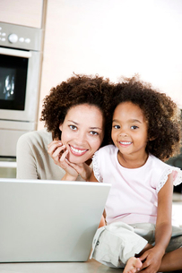 Mother and daughter with laptop in the kitchen at homeの写真素材 [FYI02119687]