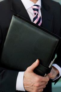 Businessman holding a leather case with briefing papersの写真素材 [FYI02119690]