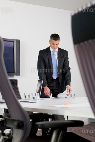 Businessman reviewing paperwork on table in conference roomの写真素材 [FYI02119722]