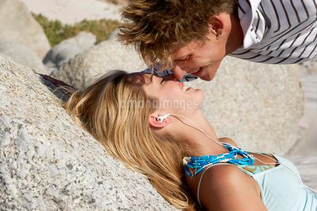 Teenage couple (17-19) relaxing on rocky beach, boy bending down to kiss girl, smiling, profileの写真素材 [FYI02119725]