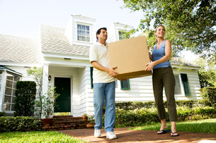 Couple moving into their new home, carrying a packing boxの写真素材 [FYI02119747]