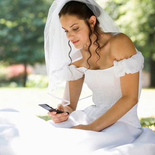 A bride using a mobile phoneの写真素材 [FYI02119785]