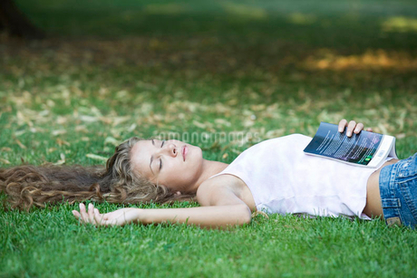 A teenage girl laying in a parkの写真素材 [FYI02119805]