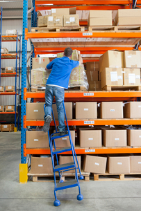 Ladder tilting under worker reaching for cardboard box in distribution warehouseの写真素材 [FYI02119807]